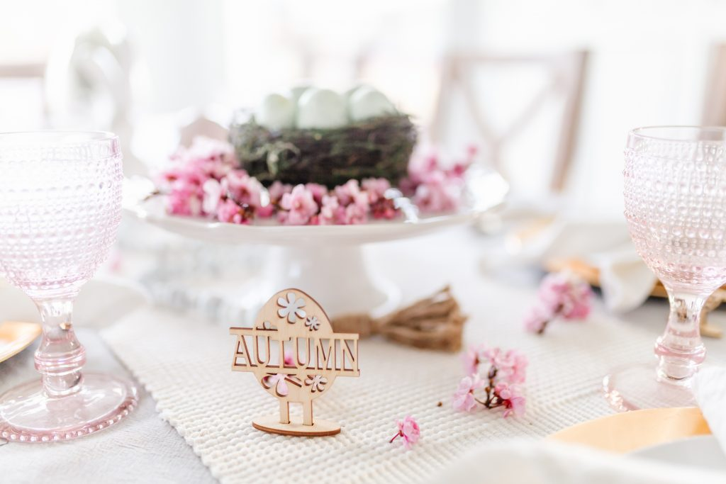 A pink and gold easter table setting with wooden name place setting