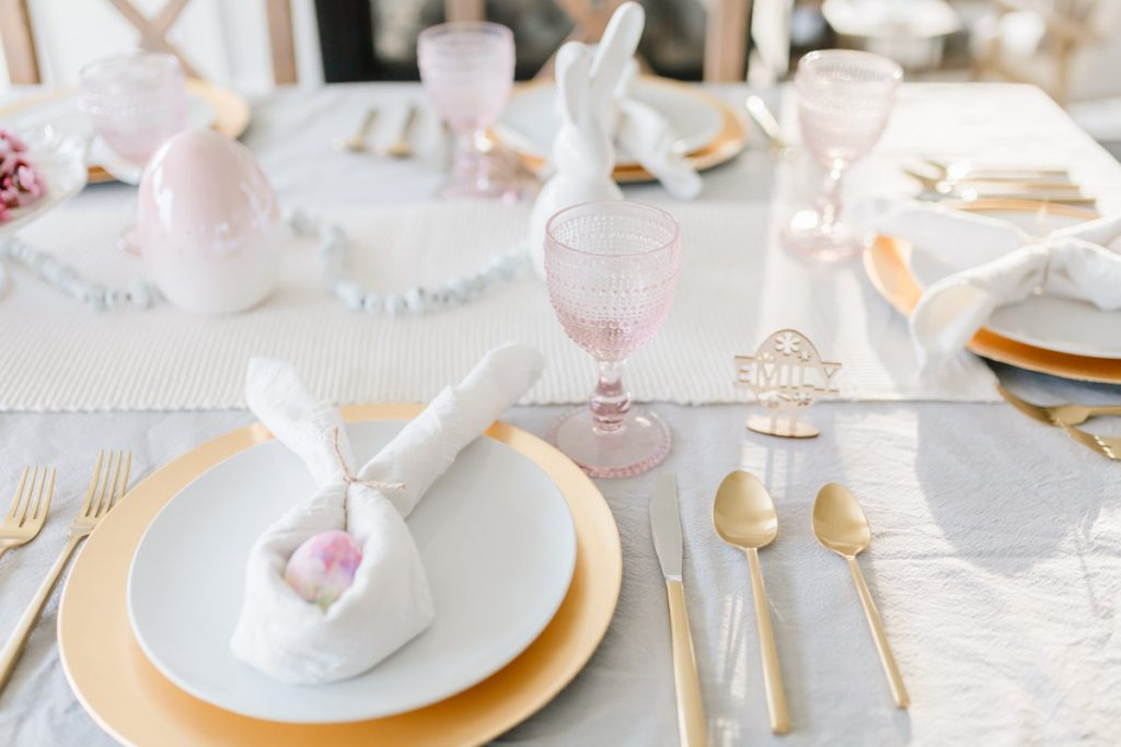 A pink and gold easter table setting with bunny napkin