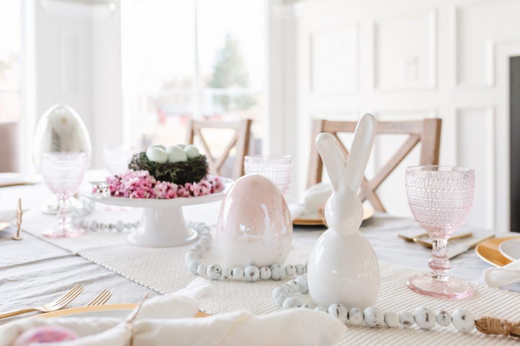 A pink and gold easter table setting with white bunny