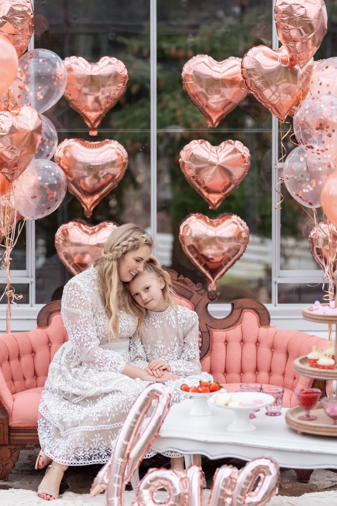 mother and daughter matching dress in front of valentines decorated greenhouse